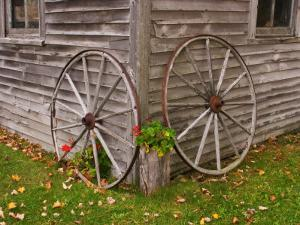 Old Wooden Barn with Wagon Wheels in Rural New England, Maine, USA by Joanne Wells