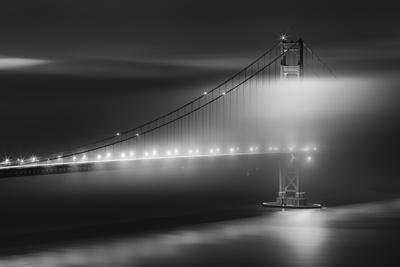 Black And White View Of The Golden Gate Bridge At Night With Silky Low Fog Around The Tower