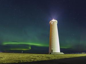 Lighthouse In Iceland With The Northern Lights Swrapping Around by Joe Azure