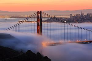 San Francisco At Sunrise, Behind The Golden Gate Bridge And A Low Blanket Of Fog by Joe Azure