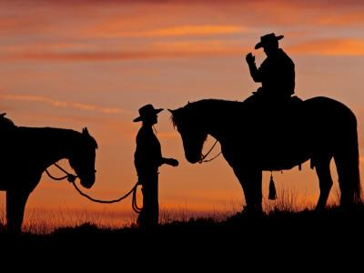 Cowboy and Cowgirl Silhouetted on a Ridge in the Big Horn Mountains, Wyoming, USA