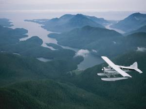 A Beaver Airplane on Floats Flies over Islands and Snowy Mountains by Joel Sartore