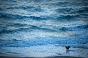 A Couple Plays in the Ocean Waves at Dusk at Riviera Beach by Joel Sartore