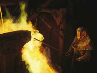 A Man in Protective Gear Tends a Smelter at Magma Metals Company