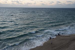 A Man Walks Along the Beach of the Florida Coast by Joel Sartore