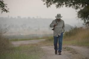 A Man Walks Through Queen Elizabeth National Park by Joel Sartore