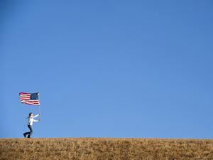 A Teenage Girl Runs across a Field with an American Flag by Joel Sartore