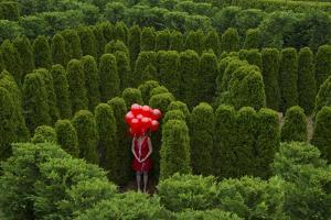 A Young Woman Stands with Balloons in the Garden Maze at Luray, Virginia by Joel Sartore