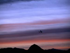 Aircraft and Mountains Silhouetted Against a Dramatic Sky at Dusk, Wyoming by Joel Sartore