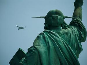 An Airplane Flies Near the Statue of Liberty by Joel Sartore