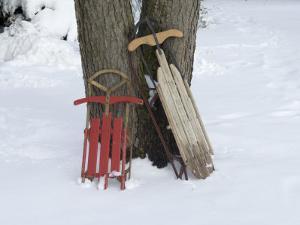 Antique Sleds in the Snow on a Family Farm near Cortland, Nebraska by Joel Sartore