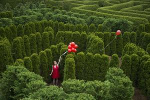 Balloons Drift Away from a Young Woman in the Garden Maze at Luray, Virginia by Joel Sartore