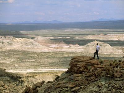Environmental Activist Observes the Rock Formations of Adobe Town by Joel Sartore