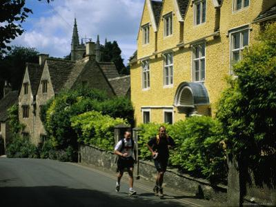 Hikers Jog Along a Street in the Village of Castle Coombe by Joel Sartore