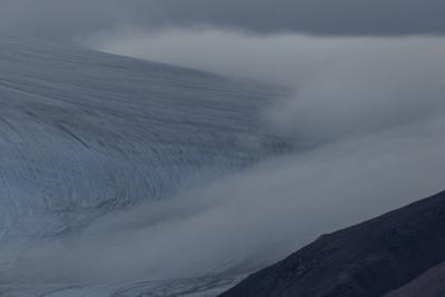 Inland ice glacier with wall of fog approaching. by Joel Sartore