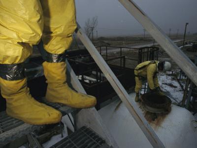 Men in Protective Clothing Check Hazardous Chemical Storage Tanks