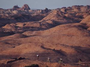 Mountain Bike Riders on Slickrock Trail Near Moab, Utah; Arches National Park is in the Background by Joel Sartore