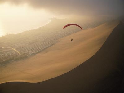 Ocean Gusts Keep a Paraglider Aloft Above Cerro Dragon, a Desert Dune by Joel Sartore