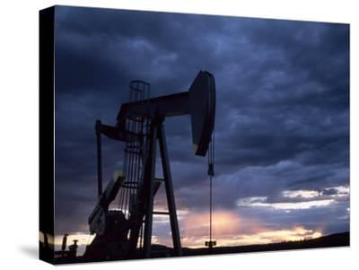 Oil Rig Silhouetted at Sunset, Adobe Town, Wyoming by Joel Sartore