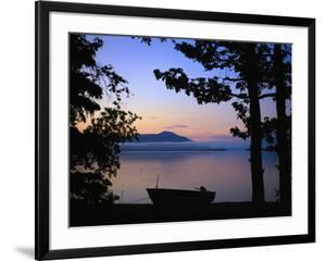 Silhouette of a motor boat on the shores of a bay in Alaska by Joel Sartore