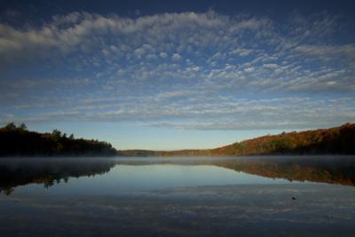 Sunrise at Walden Pond in the autumn. by Joel Sartore