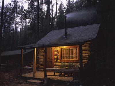 Wood Smoke Rises from the Chimney of a Log Cabin by Joel Sartore