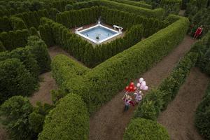 Young Girls Run with Balloons Through the Garden Maze at Luray, Virginia by Joel Sartore
