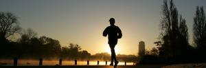 Jogger Silhouetted Against the Rising Sun as He Runs Past the Serpentine Lake in Hyde Park, London