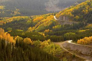 A Road Meanders Through the Brilliant Fall Colors of the San Juan Mountains of Colorado by John Alves