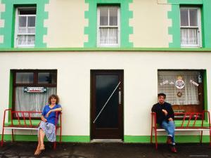 Man and Woman Sitting Outside Pub Entrance, Adrigole, Munster, Ireland by John Banagan
