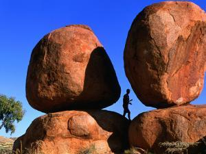 Man Standing in Between Boulders, Devil's Marbles Conservation Reserve, Australia by John Banagan