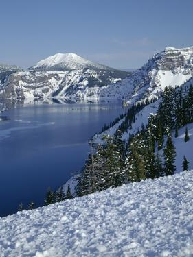 OR, Crater Lake NP. Evening light warms snowy rim of Crater Lake in late afternoon by John Barger