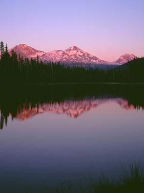 OR, Willamette NF. Sunset reddens the Three Sisters which reflect in Scott Lake. by John Barger