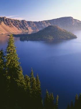Oregon, Crater Lake NP. Sunrise on west rim of Crater Lake with Wizard Island and distant Llao Rock by John Barger