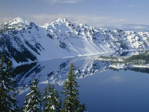 Oregon. Crater Lake NP, winter snow on west rim of Crater Lake with The Watchman and Hillman Peak by John Barger