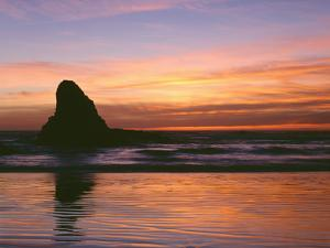 USA, Oregon. Ecola State Park, sunset over sea stack at Indian Beach. by John Barger