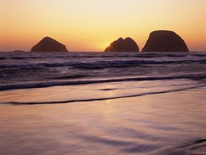 USA, Oregon, Oceanside Beach State Wayside. Sunset over Three Arch Rocks. by John Barger