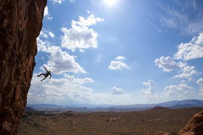 A Man Rappelling on the Red Rock Cliffs of Saint George, Utah