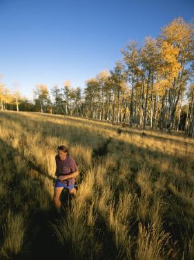 A Man Runs Through a Meadow of Tall Grass Near Mt. Elden by John Burcham