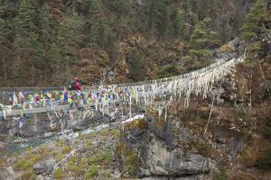 A Man Trekking across a Cable Bridge Strewn with Tibetan Prayer Flags in Khumbu Valley by John Burcham