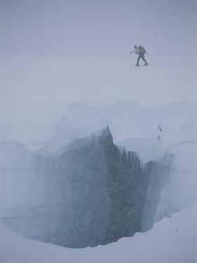 A Skier Above a Deep Glacier Crevasse by John Burcham