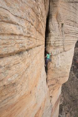 A woman rock climbing a sandstone wall in Sedona. by John Burcham