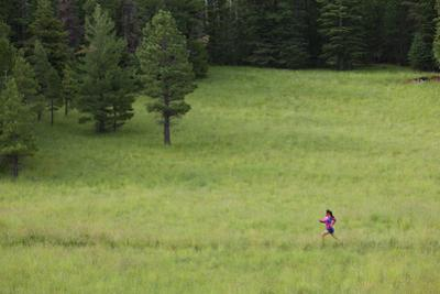 A Woman Trail Running in a Field by John Burcham