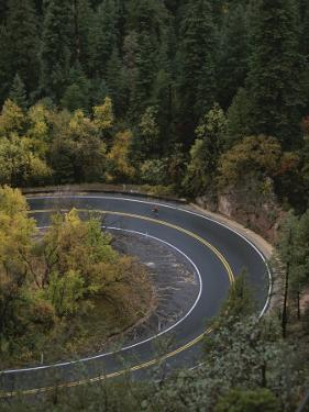 Aerial View of a Runner on a Winding Road in Oak Creek Canyon by John Burcham