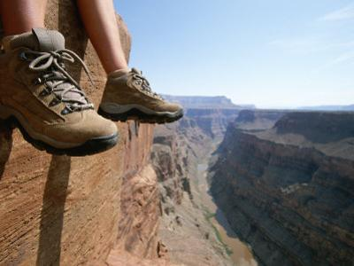 The Boot-Shod Feet of a Hiker Dangle over the Side of a Cliff