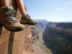 The Boot-Shod Feet of a Hiker Dangle over the Side of a Cliff by John Burcham