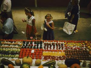 1955: Fairgoers as They Look at a Display of Produce at the Iowa State Fair, Des Moines, Iowa by John Dominis