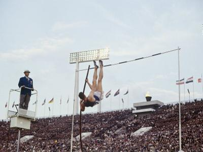 Athlete Clearing the Pole Vault at Summer Olympics