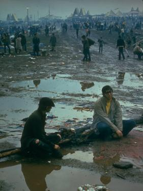 Chuck Morgan Sitting in the Mud and Water with a Friend, During Woodstock Music and Art Fair by John Dominis