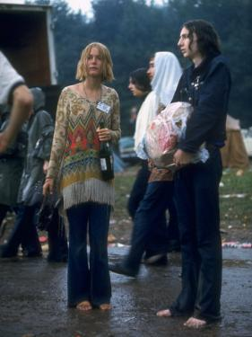 Couple Standing Barefoot on a Road Holding a Bundle and Wine Bottle, Woodstock Music and Art Fair by John Dominis